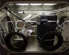 Das CCF‐Experiment in der Microgravity Glovebox der Internationalen Raumstation. Zu erkennen sind das Experimentmodul mit dem Strömungskanal (in schwarz), die Kameras, die das Signal direkt zum Boden übertragen und der Steuerungscomputer (in silber). Der Einbau fand durch die seitlichen Öffnungen der MSG statt. Danach wird die MSG wieder an ihren Platz geschoben und abgedeckt, damit kein Streulicht die Aufnahmen stört. Quelle: NASA