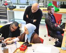 """Die Studierenden Hisham Al-Wanni, Farah Atour und Ghaith Al-Shishani (v.l.) gemeinsam mit ihrem wissenschaftlichen Betreuer Prof. Nabil Ayoub bei der Vorbereitung ihres Experiments zum Thema """"Stabilizing the electrodynamic tether by using tilger""""."""
