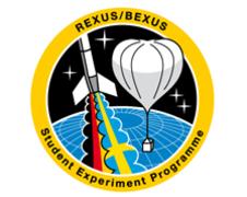 Logo des REXUS/BEXUS-Projekts Nach dem Test aller Experimente und Systeme wird die fertig zusammengebaute REXUS-Rakete zur Startrampe gebracht. Deutlich sind alle Elemente der Rakete zu erkennen: die Spitze, die Experimentmodule (dunkelblau), das Servicemodul (hellblau), das Bergungssystem (schwarz mit DLR Logo), der Motoradapter (schwarz) und der Motor mit den Finnen. (QUELLE:DLR)